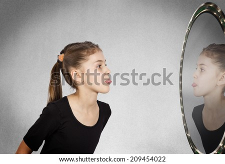 Closeup side view profile portrait child, girl sticking her tongue out looking in the mirror, isolated grey wall background. Human facial expressions, emotions, feelings, life perception body language - stock photo