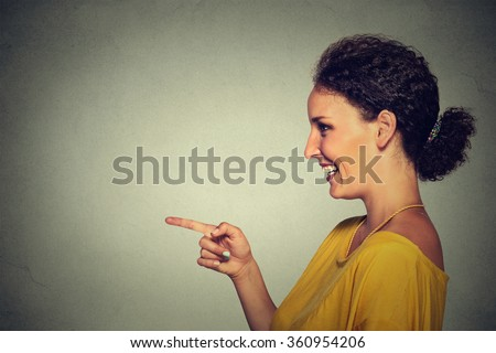 Closeup side view profile portrait of attractive woman pointing and laughing at someone or something isolated on gray wall background - stock photo