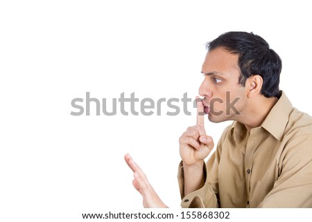 Closeup side view profile portrait of handsome man placing fingers on lips as if to say shhh, isolated on white background with copy space - stock photo