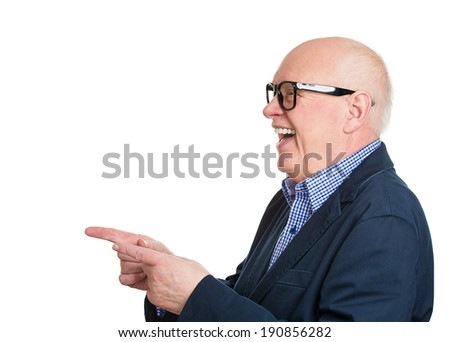 Closeup side view profile portrait senior man in glasses, laughing, pointing with finger at someone, isolated white background. Positive human face expressions, emotions, feelings, attitude, approach - stock photo
