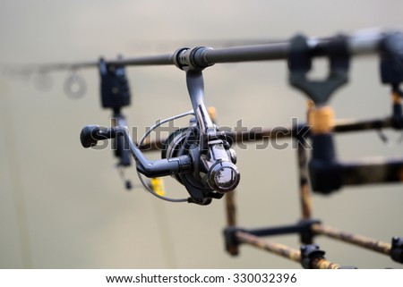 Closeup silhouette of fish-tackle fishing reel rods and rings with gray blurred natural water background, horizontal picture - stock photo