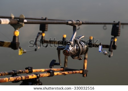 Closeup silhouette of fish-tackle fishing rods reel and rings with gray blurred natural water background, horizontal picture - stock photo