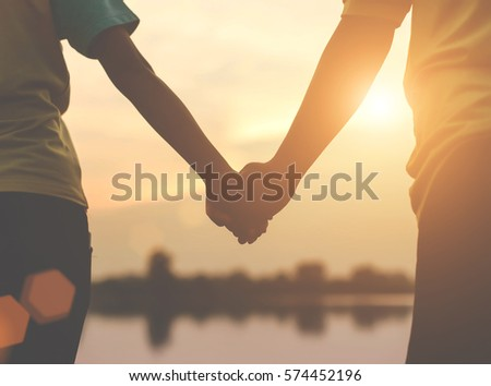 closeup silhouette of loving couple holding hands while walking at sunset