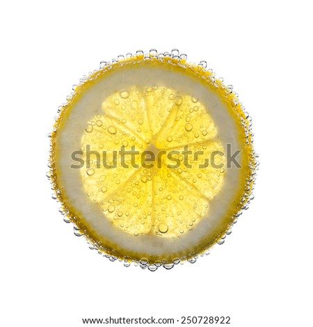 Closeup slice of lemon underwater, in drink, with bubbles, white background. - stock photo