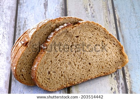 Closeup sliced of freshly baked whole wheat brown bread on wooden tile background