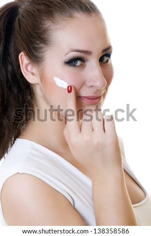 Closeup smiling woman portrait with cream on face over white background - stock photo