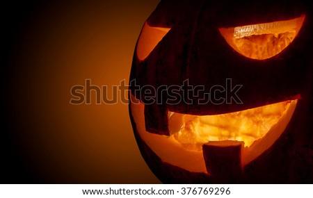 Closeup spooky halloween pumpkin Jack O Lantern shiny inside - stock photo