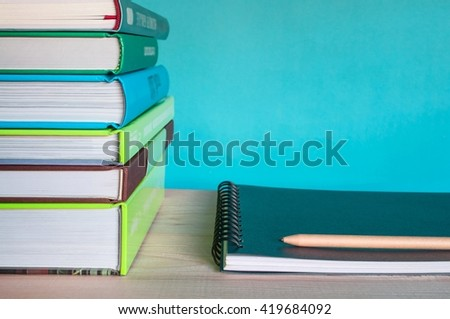 Closeup Stack of colorful books, sketchbook and pen on wooden table with blue background.
