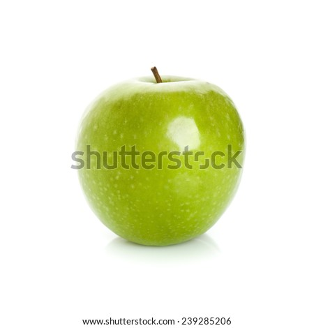 Closeup studio photo of green apple isolated on white background with soft shadow and reflection on the table - stock photo