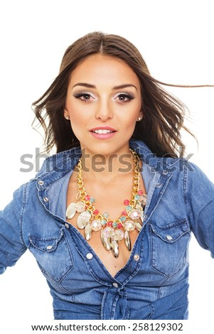Closeup studio portrait of gorgeous modern young Caucasian brunette woman smiling. Beautiful girl in blue denim shirt and modern necklace posing isolated on white background. Retouched, vertical. - stock photo