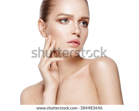 Closeup studio portrait of young beautiful model with professional makeup on white background. Perfect fresh clean skin. Deep blue eyes. Brunette hair. One hand touching head. Isolated - stock photo