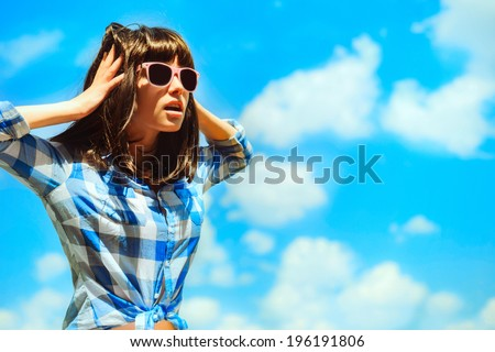closeup summer portrait of pretty young brunette woman in glasses posing near the blue sea and summer and having fun