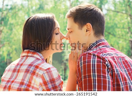 Closeup sweet young couple in love outdoors, sunny day - stock photo