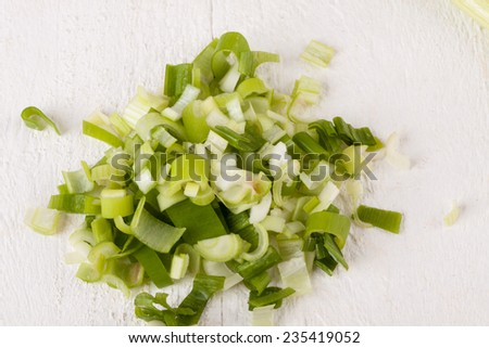 Closeup texture of a pile of diced fresh leeks with a whole one behind for use as an ingredient and vegetable in savory cuisine - stock photo