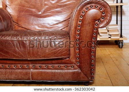 Closeup texture of vintage brown leather armchair in  library room - stock photo