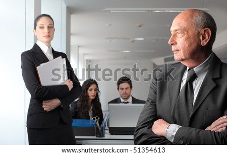 Closeup to a senior businessman and other business people on the background - stock photo