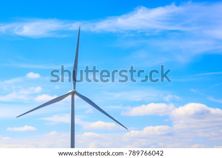 Closeup to Electric wind turbine with blue sky and clouds with copy space.