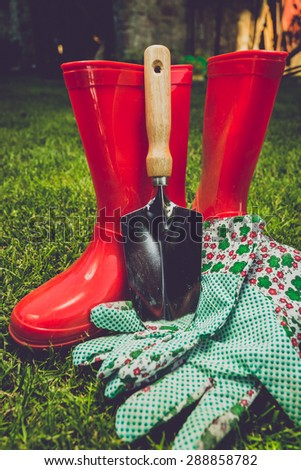 Closeup toned filter of garden tools and red boots on meadow - stock photo
