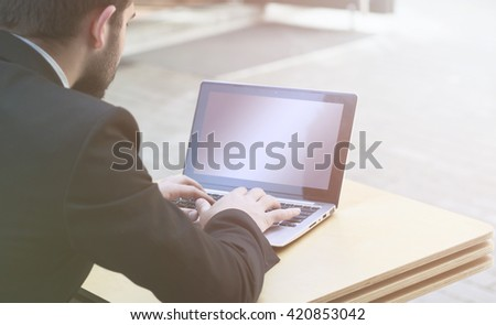 Closeup toned image of businessman using laptop computer. Blank screen may be used for many business ideas, concepts, strategies, projects, etc. - stock photo