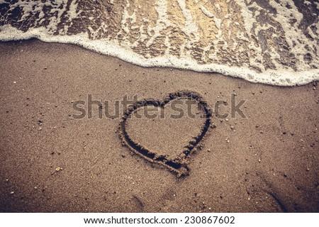 Closeup toned photo of heart drawn on sand sea beach - stock photo