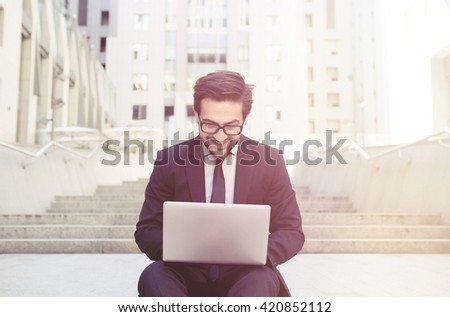Closeup toned picture of handsome businessman working on his laptop computer and smiling. Freelance man looking ar screen and happy typing messages. - stock photo