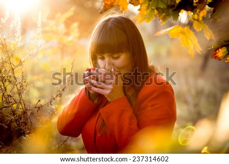 Closeup toned portrait of elegant cute woman drinking tea at cold autumn day at park - stock photo