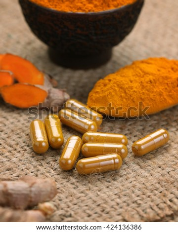 Closeup Turmeric capsules and turmeric powder on wooden table. - stock photo
