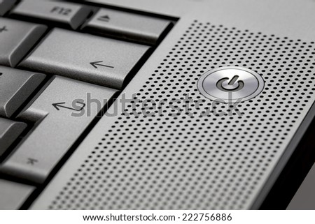 Closeup up of silver computer laptop selective focus on standby on button ideal for technology business start power symbol - stock photo