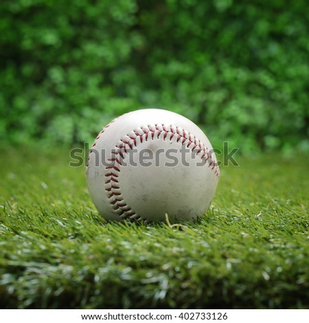 Closeup used baseball on green grass.