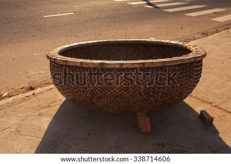 closeup Vietnamese brown round large fishing basket with dark shade stands on asphalt pavement - stock photo