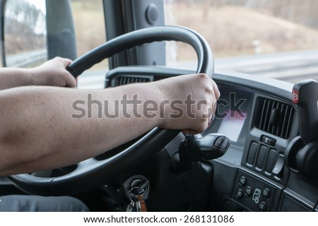 Closeup view from the truck cab. Truck driver keeps driving wheel with both hands.. Navigation is mounted on the vehicle dashboard.  - stock photo
