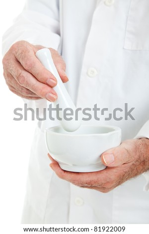 Closeup view o a pharmacist's hands, using a mortar and pestle. - stock photo