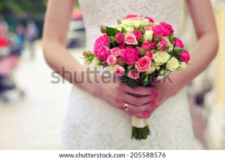 Closeup view of a bride holding bouquet of roses  - stock photo
