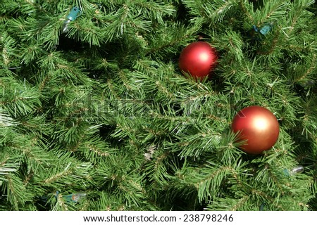 Closeup view of a Christmas tree with ornaments and lights. Ideal for use as a background. - stock photo