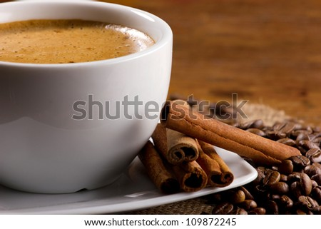 closeup view of a cup of coffee with cinnamon sticks and coffee beans