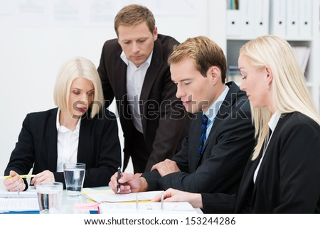 Closeup view of a dedicated professional business team grouped together around a table at the office with serious expressions analyzing and brainstorming the paperwork in front of them - stock photo