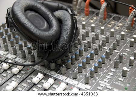closeup view of a DJ's mixing desk with a pair of headphones - stock photo