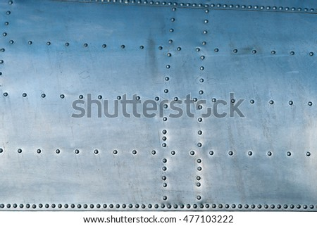Closeup view of a fuselage area of an old aircraft. Old and used aluminum plates and a pattern of rivets. Bluish color of metal