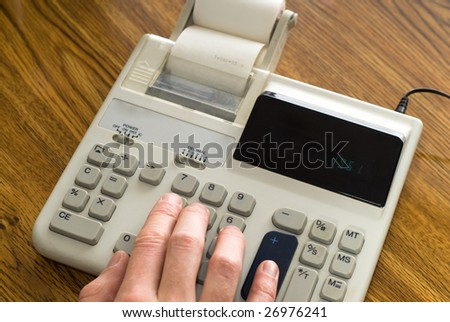 Closeup view of a hand using an adding machine on a wooden desk - stock photo
