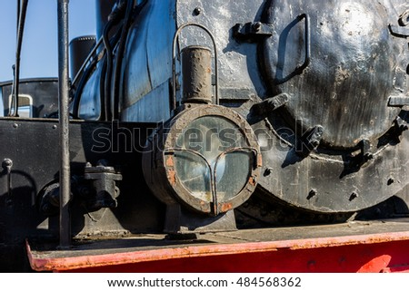 Closeup view of a headlight of the ancient steam locomotive. Petroleum lamp and a metal reflector inside the metal cage. Horizontal photography