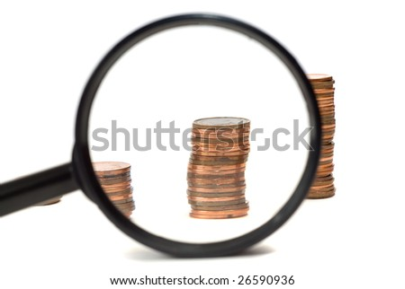 Closeup view of a magnifying glass looking at a stack of pennies, isolated against a white background