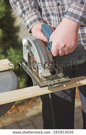 Closeup view of a man in a checkered shirt that is cutting wooden board by electric jigsaw outdoors.