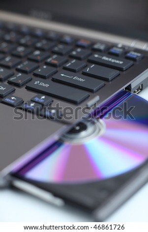 Closeup view of a modern high-end laptop computer with its CD/DVD optical drive open (shallow DOF) - stock photo