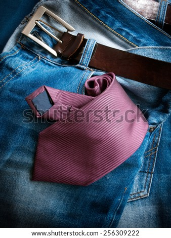 Closeup view of a necktie in the pocket of jeans trousers. - stock photo