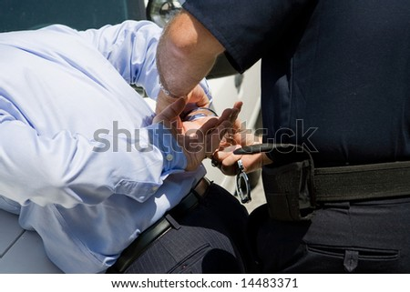 Closeup view of a police officer handcuffing a businessman. - stock photo