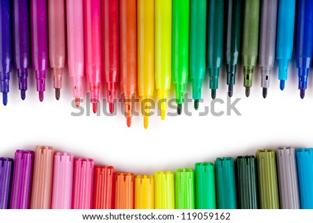 Closeup view of a row of colorful felt tip pens over white background