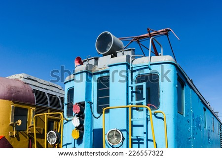 Closeup view of a service electrical railroad engine of blue color against the background of clear blue sky. Transport technology of the past. - stock photo