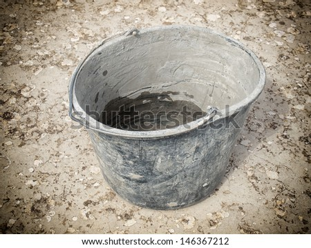 Closeup view of a used masonry bucket on a concrete floor. - stock photo