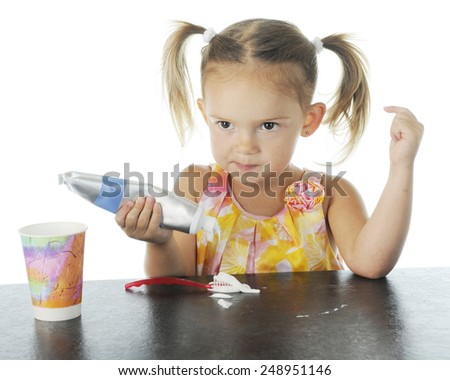 Closeup view of an adorable preschooler smugly looking up as she squeezes toothpaste on her brush.  On a white background. - stock photo