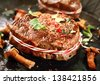 Closeup view of an appetizing grilled medallion of fillet and wild mushrooms seasoned with spice and fresh herbs - stock photo